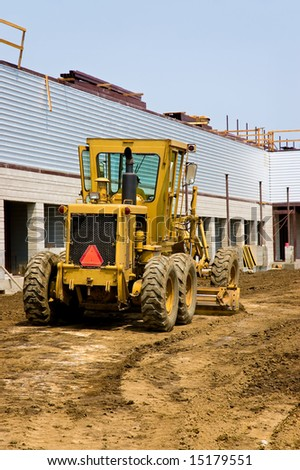 A road grader smoothing the ground around a new building