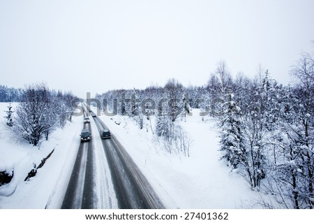 A road in winter during a snow storm - stock photo