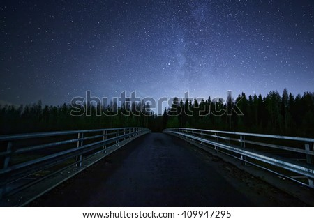 A road leading into night sky full of stars and visible milky way. A Bridge and dark forest on the foreground. - stock photo