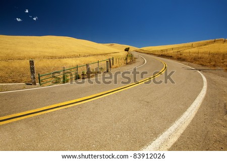 A road leading to windmills in California. - stock photo