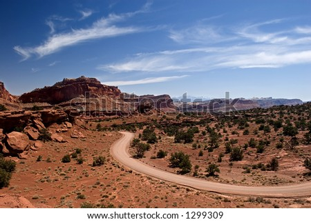 A road near Capital Reef Utah, USA winds through the warm desert. - stock photo