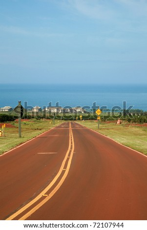 a road on maui leading down the mountian to the pacific ocean on the west side of the island - stock photo