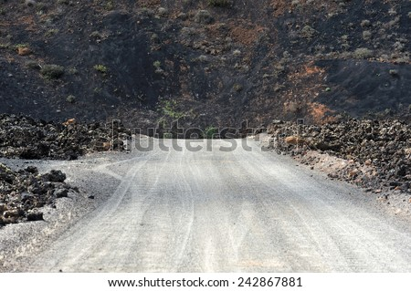 a road on wild volcanic landscape at  Lanzarote Island, Canary Islands, Spain