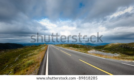 A road over mountain top with a moody sky - stock photo