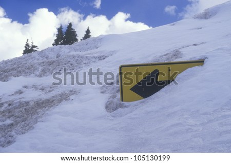 A road sign covered by snow - stock photo