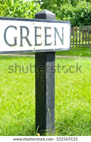 A road sign for a green, in a UK village with grass and bushes in the background - stock photo