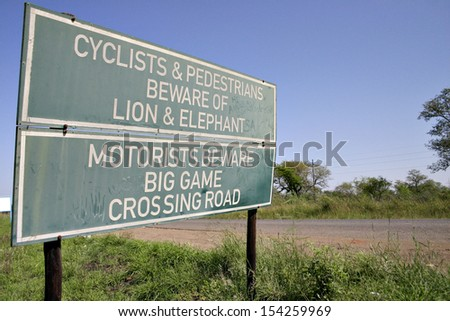 A road sign warns pedestrians and cyclists to beware of lions and elephants on a road in Swaziland, Africa. - stock photo