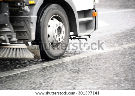 A road sweeping vehicle adjusted a sidewalk with cobblestones of dirt / Street cleaning vehicle                 - stock photo