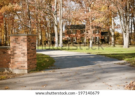 A road that leads to a brick house. - stock photo