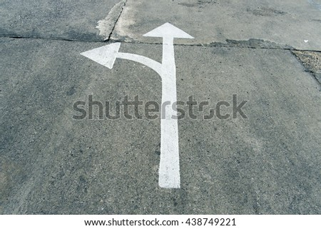 A road white arrow two way on concrete background