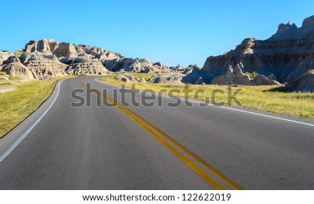 a road winding through badlands and grasslands at Badlands National Park - stock photo