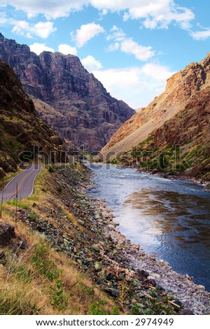 A road winds alongside the Snake River through Hell's Canyon. - stock photo