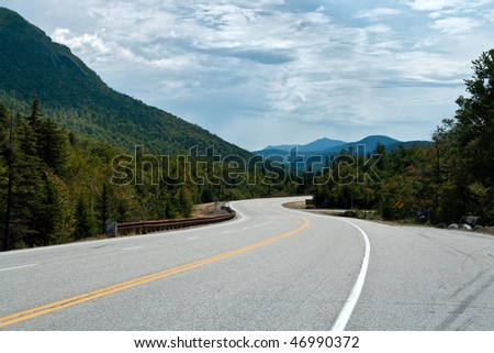 A road winds through a mountain pass in horizontal perspective - stock photo