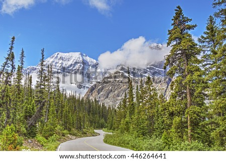 A road  winds through the Rocky Mountains in Jasper National Park - Alberta, Canada - stock photo