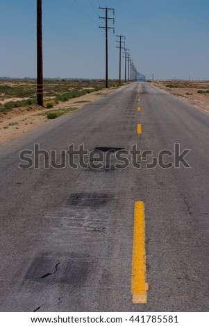 A road with a dashed yellow line leads to the horizon in the desert. - stock photo