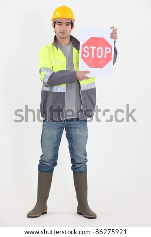 A road worker holding a stop sign. - stock photo