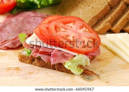 A roast beef sandwich being prepared - stock photo