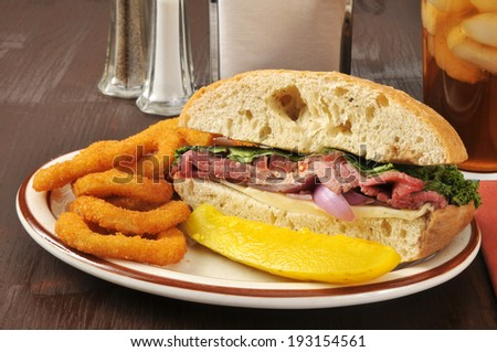 A roast beef sandwich on ciabatta bread with onion rings