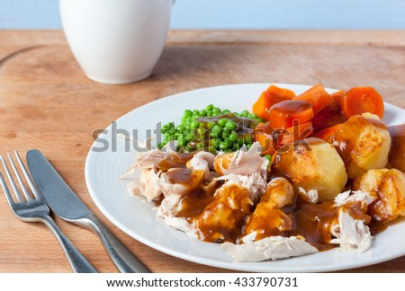 A roast chicken dinner on a white plate with cutlery and a gravy boat in the background