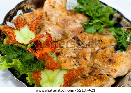 a roasted chicken cut and decorated with cucumber flowers, parsley and dill