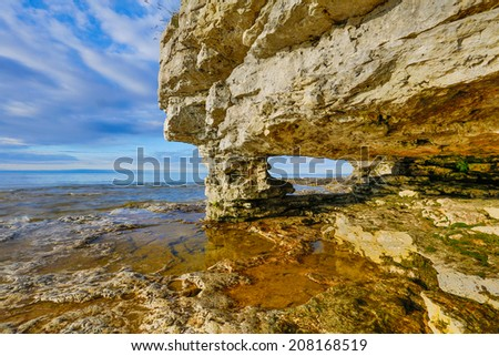 A rock arch window has been eroded by the waves at Door County, Wisconsin's Cave Point  with a cloudy blue sky. - stock photo