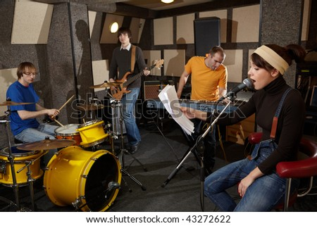 a rock band is working in studio. vocalist girl is singing with text of song in the her hand - stock photo