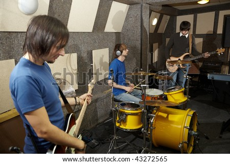 a rock band. two musicians with electrical guitars and one drummer working in studio - stock photo