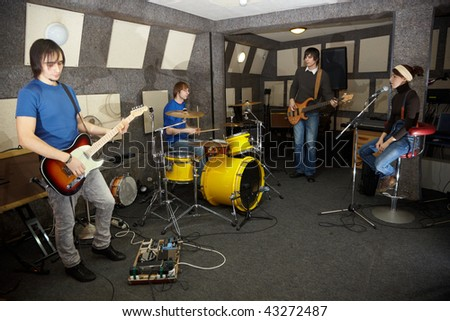 a rock band. vocalist girl, two musicians with electrical guitars and one drummer is working in studio - stock photo