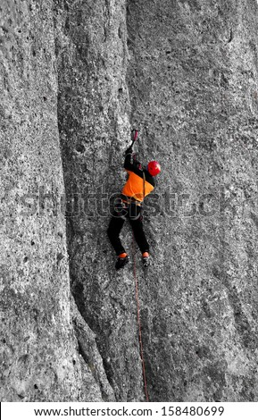 A rock climber advancing on a steep rock wall - stock photo