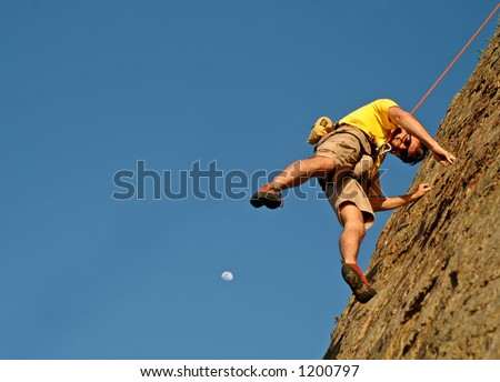 A rock climber baleys off cliff as moon rises - stock photo