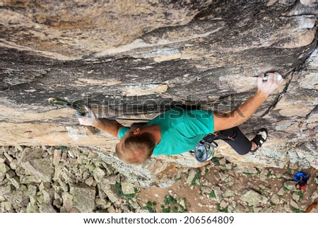 A rock climber clips his protection bolt on a route in the Utah mountains, USA. - stock photo