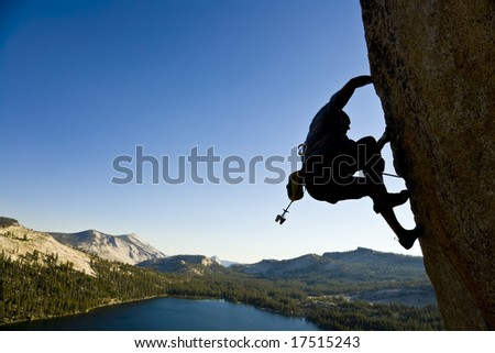A rock climber desperately clinging to a rock face in Yosemite National Park, California, on a summer day. - stock photo