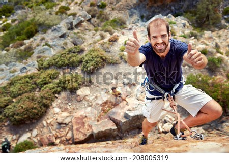 A rock climber with rock climbing equipment on holding a thumbs up and smiling at  the camera - stock photo
