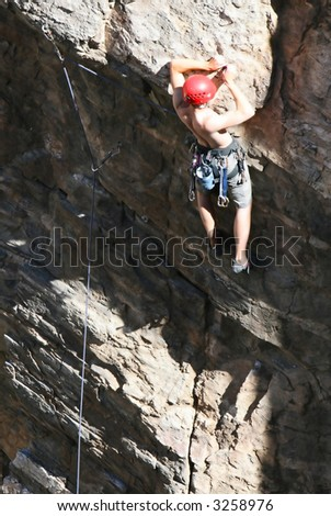 A rock climber works his way up a rock face protected by a rope clipped into bolts. He is wearing a helmet and quickdraws dangle from his harness. The route is in the desert southwest United States.