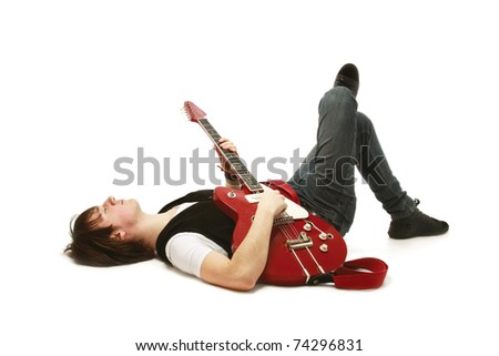 A rock guitarist lying on the floor - stock photo