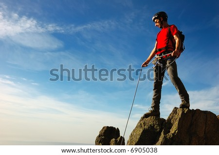 A rock / mountain climber at the summit of his climb, basking in brilliant sunshine. West Alps, Italy.