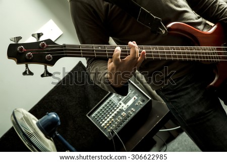 A rock musician playing the bass in a rehearsal room.  - stock photo