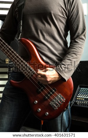 A rock musician playing the bass in a rehearsal room.