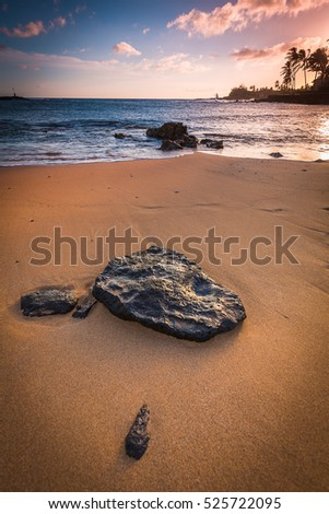 A rock on a sandy beach at sunset/sunrise in Kauai Hawaii
