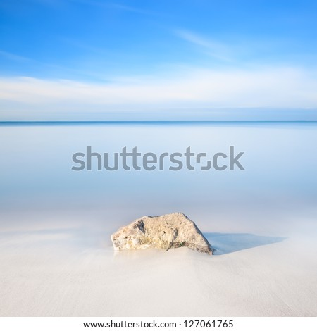 A rock on a white sand beach and blue ocean on horizon. Long exposure photography. - stock photo