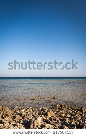 A rocky beach of the Red Sea on the Egyptian coast with blue sky copy space. - stock photo