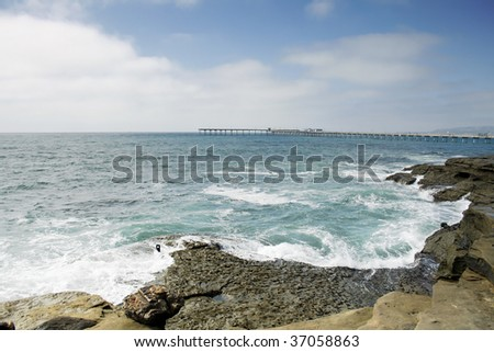 A rocky ocean setting with a pier far off in the distance. - stock photo