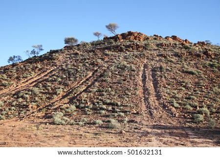 A rocky red hill in Australia's desert outback with vehicles tracks up the side of it.