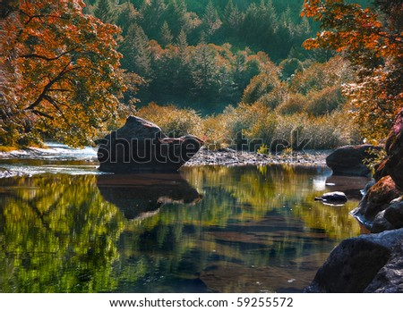 A rocky river with waters so calm it is almost like a lake. This photograph was taken in Oregon. - stock photo