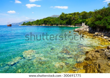 A rocky shore, boats and a ship, in the Kolocep Island, one of the Elaphiti Islands, Croatia - stock photo