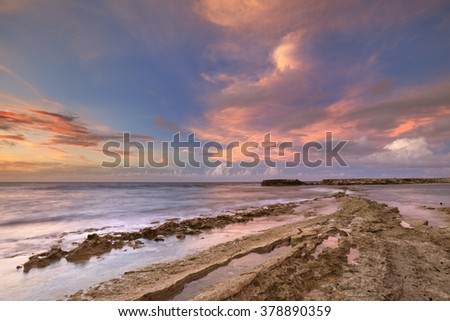A rocky tropical coast at sunset. Photographed at Playa Canoa on Curacao, The Netherlands Antilles. - stock photo