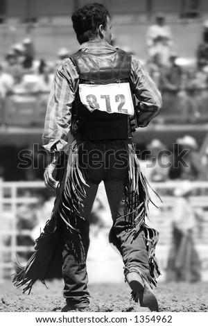 A Rodeo Cowboy walks back to the chutes after a successful ride (shallow focus, black and white). - stock photo