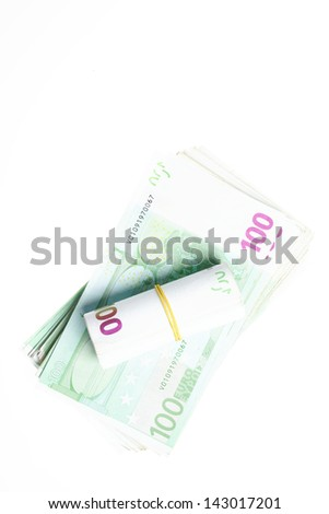 A roll of 100 Euro bills laying over a stack of the same bills on a white background.