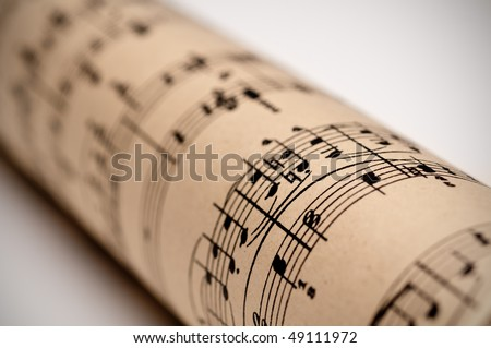 a roll of sheet music on old discolored parchment - stock photo