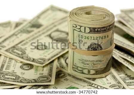 A roll of twenty dollar bills on a pile of one dollar bills - stock photo